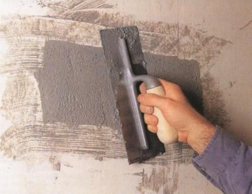 Замазывание дыры в стене шпателем